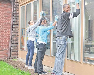 Youngstown Connection members, from left, Alexis Shellow of Youngstown, Arielle Green of Austintown and Leon Smith of Liberty clean the windows of the Burdman Group as part of United Way of Youngstown and the Mahoning Valley's 10th annual Youth Day of Caring on Saturday.