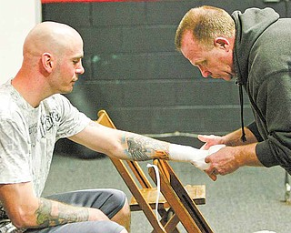 Boxing trainer Jack Loew wraps the hand of Youngstown's Kelly Pavlik before a recent sparring match with  Romero Johnson at the Southside Boxing Club. In the recent weeks, Pavlik (36-2, 32 KOs) has been getting  ready for his comeback bout against Alfonso Lopez (21-0, 16 KOs), a 10-round, 171-pound undercard bout  schedule for May 7 at the MGM Grand in Las Vegas.