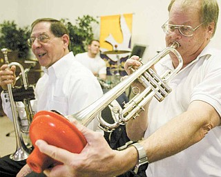 Chris Eldridge uses a plunger as a mute while playing with the Dixie Dandies. Leader Joe Commarata is at left.