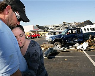 Chris Nelson, left, hugs his daughter Andrea Nelson, 15, in the parking lot in front of Lowe's hardware store in Sanford, N.C., on Sunday, April 17, 2011, a day after a tornado destroyed the building while the Nelsons were inside shopping. The Nelsons returned Sunday to reclaim their truck, back right.