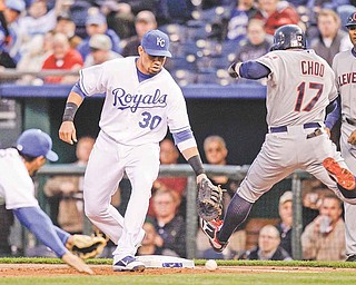 Kansas City Royals first baseman Kila Ka'aihue (30) attempts to field the baseball on an infield hit by Cleveland Indians right fielder Shin-Soo Choo (17) during the first inning of a major league baseball game Monday, April 18, 2011, in Kansas City, Mo.