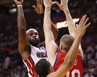 Miami Heat's LeBron James, rear, goes up for a shot against Philadelphia 76ers' Spencer Hawes (00) and Evan Turner, foreground, during the first quarter of Game 2 of a first-round NBA playoff basketball series, Monday, April 18, 2011 in Miami.