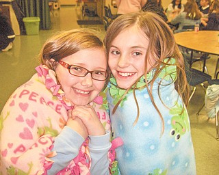 A heartwarming trend: Jayda Benson, at left, and Katherine Kali, fourth-grade students at Holy Family School on Center Road, Poland, cuddle up in blankets they made for premature babies in the special care nursery at St. Elizabeth Health Center, Youngstown. The two are members of the Acts of Random Kindness group, which recently made blankets from material donated by Melinda Miller, Jayda's mother. The blankets were delivered to the hospital, where the ARK girls viewed babies through the window and met one of the mothers, who recently delivered triplets.