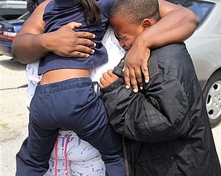 Evette Davis hugs her daughter Heaven, 5, and son Julian, 9,  after a shooting at Ross Elementary school Tuesday, April 19, 2011, in Houston.    A kindergartener who brought a loaded gun to his Houston elementary school Tuesday was among three students injured by fragments when it fired after falling from his pocket as he sat down for lunch, officials said.   One bullet was fired about 11 a.m. in the Ross Elementary School cafeteria, spraying fragments at the students, said Houston Independent School District Assistant Police Chief Robert Mock.  Two 6-year-old boys, including the one who had the gun, were wounded in the foot, said district spokesman Jason Spencer. A 5-year-old girl also suffered a foot injury.