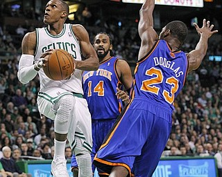 Boston Celtics point guard Rajon Rondo (9) drives to the basket through the defense of New York Knicks guard Toney Douglas (23) and center Ronny Turiaf (14) during the first quarter of Game 2 of a first-round NBA basketball playoff series, in Boston on Tuesday, April 19, 2011.