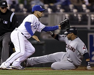 Cleveland Indians' Carlos Santana, right, beats the tag by Kansas City Royals third baseman Mike Aviles, left, to advances to third on a single by Travis Hafner during the ninth inning of a baseball game Wednesday, April 20, 2011, in Kansas City, Mo.