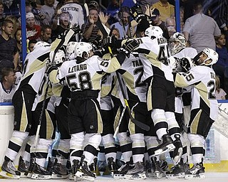 Pittsburgh Penguins players mob James Neal after he scored the game-winning goal during double-overtime in Game 4 of a first-round NHL Stanley Cup playoff series on Wednesday, April 20, 2011 in Tampa, Fla.