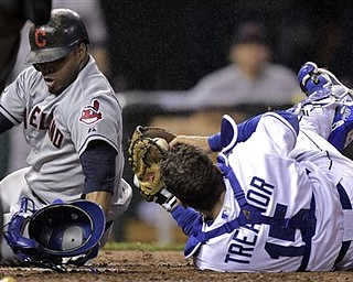 Cleveland Indians' Carlos Santana, left, collides with Kansas City Royals catcher Matt Treanor (15) while trying to score on a single hit by Travis Hafner during the eighth inning of a baseball game Thursday, April 21, 2011, in Kansas City, Mo. Santana was out on the play. (AP Photo/Charlie Riedel)