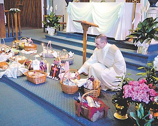 Nick Moliterno, deacon at Immaculate Heart of Mary Church in Austintown, lights candles near Easter baskets filled with parishioners' holiday food.