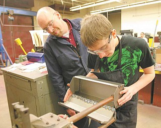 Instructor Michael Powell observes as first year student Rib Tullio, a freshman, spot welds a tool box he designed.