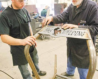 Michael Cherol and Bob Day check a weld on a Canfield Fair bench. Boardman High School's industrial arts program has made and supplied more than 100 benches for the Canfield Fairgrounds.