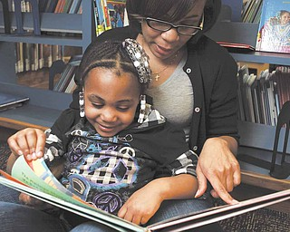 Nikida Davis, a Lakota English teacher,  reads with her daughter, Nia, 5, at the Westwood Public Library. Nikida is one of 15,397 parents who have applied for an Ohio Ed Choice voucher for a chance at a private school for Nia.