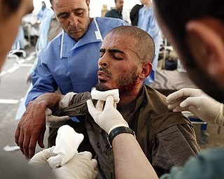 Medics work on an injured man at Hikma hospital in Misrata, Libya, Sunday, April 24, 2011. Rebel fighters drove Moammar Gadhafi's forces to the edge of the besieged western city of Misrata on Sunday, taking control of the main hospital where government troops had been holed up, a resident said.