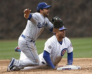 Los Angeles Dodgers second baseman Aaron Miles and Chicago Cubs' Aramis Ramirez look for the call after Ramirez overran second base and was thrown out by Dodgers left fielder Jerry Sands in the sixth inning of the Dodgers' 7-3 win in a baseball game Sunday, April 24, 2011 in Chicago.