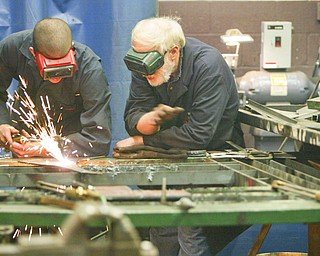 ROBERT K. YOSAY | THE VINDICATOR..Cutting a piece of metal  Tony Dundee a freshman - gets a hand from instructor Mr Bob Day . Students in addition to learning all facets of welding and cutting and working with metal they must also start and finish a metal project - ..-30-