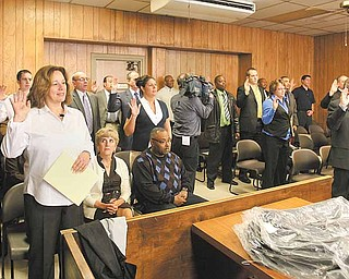 Youngstown Municipal Court Judges Elizabeth Kobly, Robert A. Douglas Jr. and Robert Milich (not pictured) swear in 30 part-time officers Monday to act as the security force in municipal court under the direction of city police.