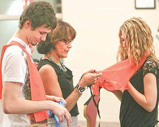 Jodi Stoyak, Liberty Township trustee, center, helps Victoria Ferry, a junior at Liberty High School, try on an orange vest that she'll be wearing as she and other student volunteers participate in the Great American Cleanup this weekend. Jacob Schriner-Briggs, also a junior, left, said the community service would benefit the township.