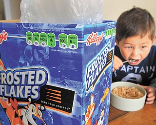 Nathaniel Donaker, 4, eats Kellogg's Frosted Flakes cereal at his home in Palo Alto, Calif., on Thursday. Commercials promoting sugary breakfast cereals could be put on a strict diet under government guidelines.