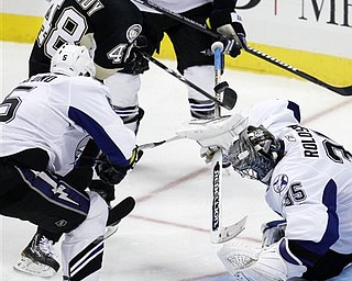 Pittsburgh Penguins' Tyler Kennedy (48) can't get his stick on a rebound off Tampa Bay Lightning goalie Dwayne Roloson (35) under pressure from Lightning defenseman Mattias Ohlund (5) during the third period of Game 7 of a first-round NHL hockey Stanley Cup playoff series in Pittsburgh on Wednesday, April 27, 2011. The Lightning won 1-0 to win the series. (AP Photo/Gene J. Puskar)