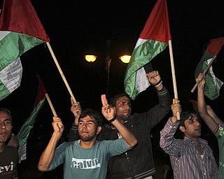 Palestinians wave flags and chant slogans in support of a reconciliation between the rival Fatah and Hamas movements, in Gaza City, Wednesday, April 27, 2011. Palestinians have reached initial agreement on reuniting their rival governments in the West Bank and Gaza, officials from both sides said Wednesday, a step that would remove a main obstacle in the way of peace efforts with Israel. (AP Photo/Adel Hana)