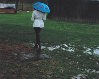 The cancellation of a Mahoning County Track Meet due to a rainfall sent Canfield High School senior high jumper Leanna Hartsough outdoors to play in the puddles.