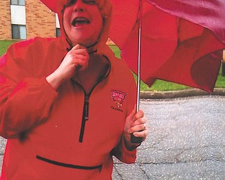 Brenda Puntel of Austintown laughs at the attempt by the wind and rain to put a damper on her first walk of spring with her friend Roseann.