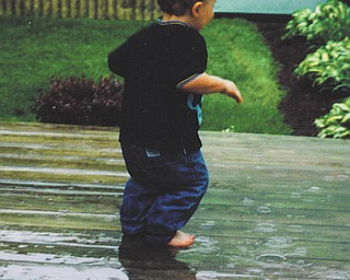 """Bryce Deloe of Moon Township, Pa., was just 2 when his grandmother, Barb Cardarelli of Struthers, snapped this picture of him """"dancing in the rain"""" on her deck for the very first time. She says it's still one of her favorite pictures."""