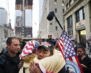 Dionne Layne, facing camera, hugs Mary Power as they react to the news of the death of Osama bin Laden, Monday, May 2, 2011 in New York. At left is the under construction 1 World Trade Center, also known as the Freedom Tower.