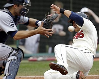 Cleveland Indians' Shin-Soo Choo, right, scores as Detroit Tigers catcher Alex Avila, left, waits for the ball in the eighth inning of a baseball game on Sunday, May 1, 2011, in Cleveland. Choo scored on a single by Orlando Cabrera. The Indians won 5-4.