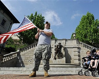 "In celebration of the announcement that Osama Bin Laden was killed, Iraq veteran Jesse Macdonald waves an American flag at Monument Terrace with his two sons on Church Street in downtown Lynchburg, Va. on Monday, May 2, 2011. ""When we say our prayers, [my daughter] always adds in, 'And may they catch the bad guys.' Today I told her, 'Last night they got the number one bad guy,'"" said Macdonald."