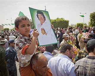 In this photo made on a government organized tour, supporters attend funeral ceremony for members Gadhafi family in Tripoli, Libya, Monday, May 2, 2011. A NATO missile strike in Tripoli killed Gadhafi's son Seif al-Arab and his three young grandchildren.