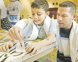 Curtis Megginson III and his son Curtis Megginson IV work on a coloring project during Family Night at Taft Elementary School on Youngstown's South Side. The boy is a kindergarten student at Taft.