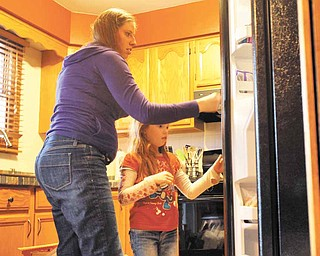 Laurie Thompson, left, is a mother of three and is a surrogate mother of twins for a couple in Spain, the second time she has been a surrogate. Thompson helps her daughter Avery open a new refrigerator at home in McHenry, Illinois, on April 4, 2011.