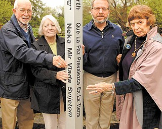 """Members of Seniors for Peace meet with Keith Kaiser, second from right, horticulture director at Mill Creek MetroParks, to admire the peace pole that will be installed and dedicated in a brief ceremony at 11 a.m. Friday in Fellows Riverside Gardens. Seniors for Peace members are, from left, the Rev. Jim Ray, Shirley Megown and Norma Coe Anderson. The message, """"May Peace Prevail on Earth,"""" is in eight languages."""