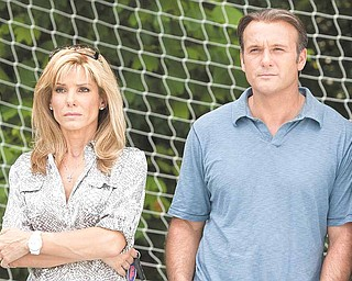 """In this film publicity image released by Warner Bros., Sandra Bullock, left, and Tim McGraw are shown in a scene from, """"The Blind Side."""""""