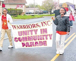 CeAnna Curtis, 9, left, and TaNia Simms, 10, lead a unity parade down Market Street on Youngstown's South Side Saturday morning.