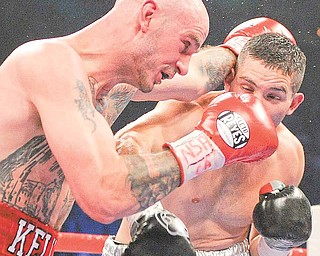 Kelly Pavlik, left, exchanges punches with Alfonso Lopez in the third round during a WBO World super bantamweight title bout, Saturday, May 7, 2011, in Las Vegas.