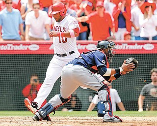 Los Angeles Angels' Vernon Wells (10) scores ahead of the throw to Cleveland Indians catcher Carlos Santana (41) on a double by the Angels' Alberto Callaspo (not pictured) during the sixth inning of a baseball game in Anaheim, Calif., Sunday, May 8, 2011.