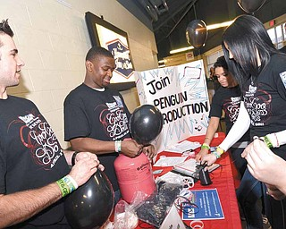 Penguin Productions members blow up black balloons as part of a pre-concert promotion for the April 12 Goo Goo Dolls show at Covelli Centre. From left are JD Kubacki, Dennis Pixley, Anastasia Seymour and Olivia Arnold.