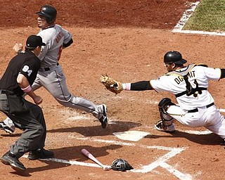Pittsburgh Pirates catcher Ryan Doumit, right, cannot get the tag on Houston Astros' Humberto Quintero, upper left, with umpire Lance Barrett (94) making the call during the seventh inning of a baseball game in Pittsburgh, Sunday, May 8, 2011. Quintero scored from second on a bunt by Astros' Angel Sanchez and an error. The Pirates won 5-4.