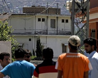 Pakistani youths view the house, background, of former al-Qaida leader Osama bin Laden in Abbottabad, Pakistan on Sunday, May 8, 2011. Osama bin Laden was killed by a helicopter-borne U.S. military force on Monday, in a fortress-like compound on the outskirts of Pakistani city of Abbottabad.