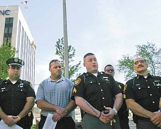 Local police and firefighters gathered in downtown Youngstown to honor officers killed in the line of duty. They are, from left, Youngstown Police Officer Sam Mosca; Christopher Weaver, Youngstown Professional Firefighters union; Sgt. T.J. Assion, Mahoning County Sheriff's Department and president of Fraternal Order of Police Lodge 141; and Sgt. Salvatore Pascarella from the sheriff's department. Monday's event was part of National Police Memorial Week, but the gathering also focused attention on the new Ohio law that limits collective-bargaining rights of public employees like police officers and firefighters.