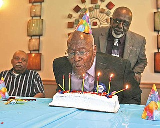 Moses Watson makes a wish as he blows out birthday candles with his friend Harold Brown.  At left is Paul Jackson, another friend. Watson celebrated his 100th birthday Tuesday at Campus Health Care Center in Liberty.