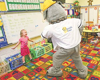 Scrappy, the mascot for the Mahoning Valley Scrappers minor-league baseball team, plays with kindergartner Jessica Hentzel who pulled his tail. The 23 students in Robin Speece's class at Austintown's Lloyd Elementary School earned a pizza party Wednesday with the mascot for reading 1,684 books since January.