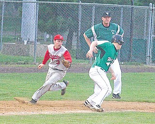 West Branch baseball co-coach Walt DeShields watches as Niles' Michael Waton (3) runs down the Warriors' Matt Edie (16) during a Division II sectional final baseball game Friday at Cene Park in Struthers. The Red Dragons downed the Warriors, 10-5, to set up a showdown with Canfield.