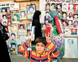 A boy holding a plastic weapon poses for a picture in front of portraits of people who were killed or have disappeared during Moammar Gadhafi's regime in Benghazi, Libya, Monday, May 16, 2011. Luis Moreno-Ocampo, prosecutor of the International Criminal Court in The Hague, announced Monday that he would seek arrest warrants against the leader of Libya, Moammar Gadhafi, his son Seif al-Islam and the country's intelligence chief on charges of crimes against humanity.