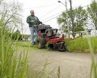John Foty of Foty's Lawn Service mows grass on Iowa Street in Girard on Tuesday. The rainy weather has slowed his business, forcing him to cut 50 to 60 fewer lawns a week.