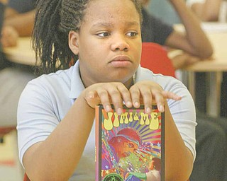 """Kelaya Banks, a sixth-grader at Wilson Middle School in Youngstown, holds a copy of author Jaime Adoff's book """"Jimi and Me."""" Adoff was visiting with students as part of Right to Read Week."""