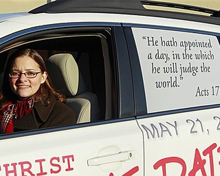 In this Dec. 17, 2010 photo in Raleigh, N.C., Allison Warden poses with her car showing a message about the rapture. Warden, of Raleigh, has been helping organize a campaign using billboards, post cards and other media in cities across the U.S. through a website, We Can Know.