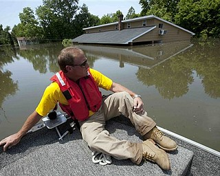Deputy Mike Traxler views flooded homes in Vicksburg, Miss., Wednesday, May 18,  2011. Floodwaters from the Mississippi river are expected to crest in Vicksburg on Thursday.   Some of the worst flooding is in the area from Vicksburg northeast to Yazoo City, along the Yazoo River. The Yazoo Backwater Levee north of Vicksburg connects with the main Mississippi River levee. The Corps of Engineers officials had predicted that at least a foot of water could pour over the top of the levee, flooding tens of thousands of more acres of farmland in the lower Mississippi Delta.